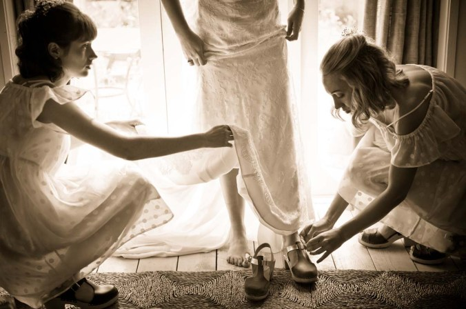 """bride putting shoes on"""